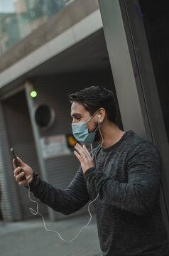 hombre con mascarilla hablando por teléfono en la calle
