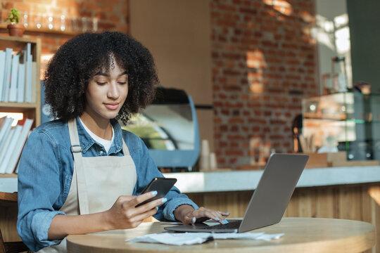 Millennial barista works in cafeteria with modern design loft interior maks documentation in online database