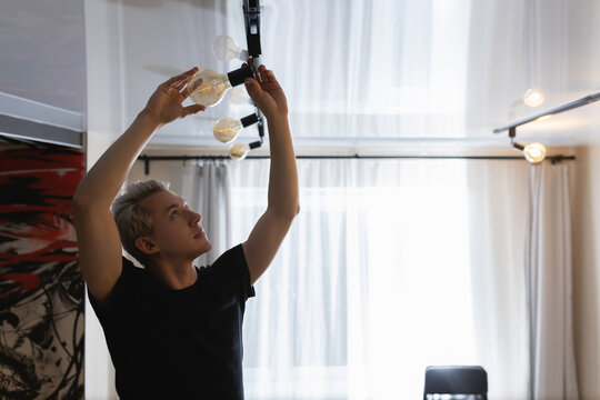 A man with white hair changes a burnt out light bulb at home