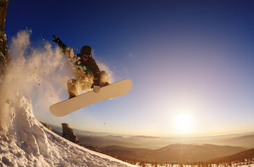 Snowboarder jumping against the sunset sky