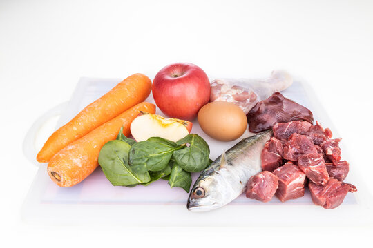 Ingredients of barf raw food recipe for dogs consisting meat, organs, fish, eggs and vegetable on chopping board