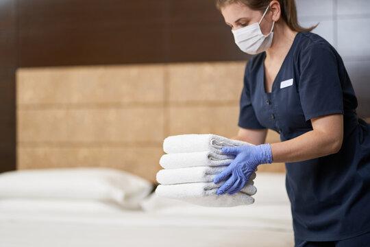 Housemaid preparing clean towels in the cleaned room