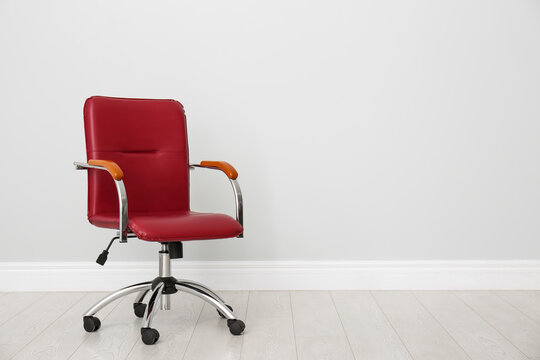 Comfortable office chair near light wall indoors. Space for text