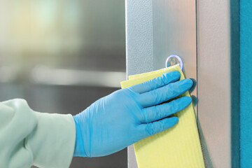 Sanitizing an elevator push button against bacteria and virus.