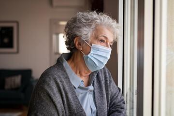 Sad senior woman wearing face mask staying at home