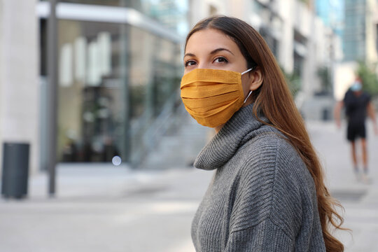 Young woman with protective mask looks around in modern city street