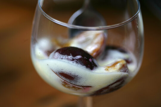 Plums with white sauce in wine glass