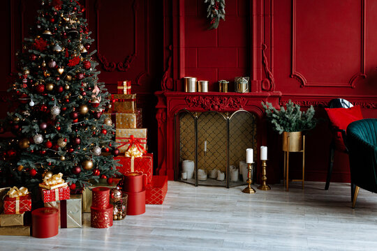 Beautiful festively decorated room with a Christmas tree. Cozy living room in red tones with a stylish classic decor.
