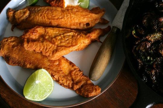Golden battered fried fish fillets with lime on plate
