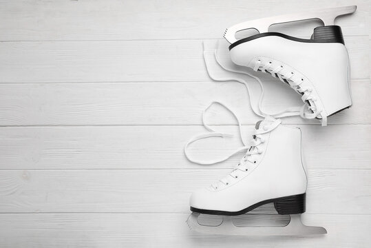 Pair of ice skates on white wooden background, top view. Space for text