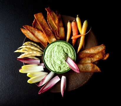 Close up of Greek dip with vegetables and toasts