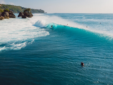 Aerial view with surfing at barrel wave. Blue perfect waves and surfer