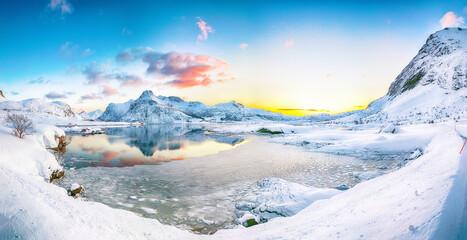 Gorgeous frozen Flakstadpollen and Boosen fjords with cracks on ice during sunrise with Hustinden mountain on background on Flakstadoya island