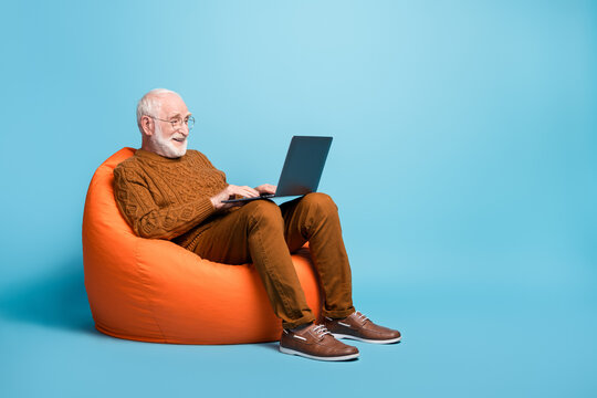 Portrait of his he nice attractive focused bearded grey-haired man sitting in bag chair using laptop writing email letter browsing web wi-fi isolated over blue pastel color background