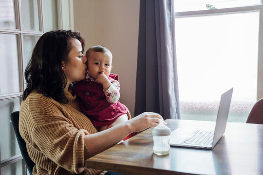 Mom holding baby and working from home on laptop at dining room table