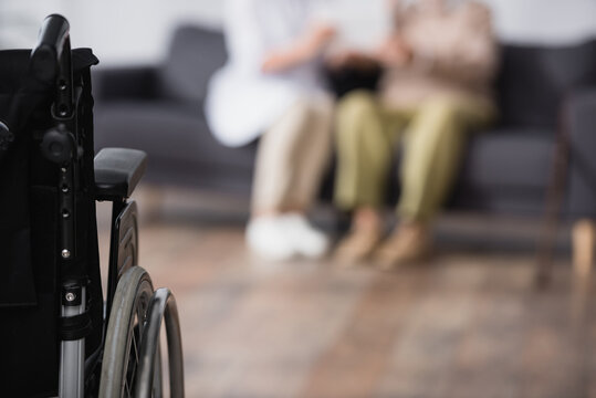 medical assistant and aged man sitting on sofa at home near wheelchair on blurred foreground