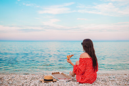 Woman having a picnic with pizza on the beach