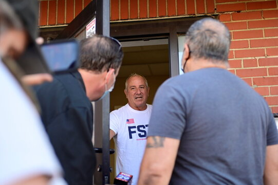 An unidentified employee in a company t-shirt answers the door of Four Seasons Total Landscaping, the site of a Trump-campaign news conference days earlier, in Philadelphia