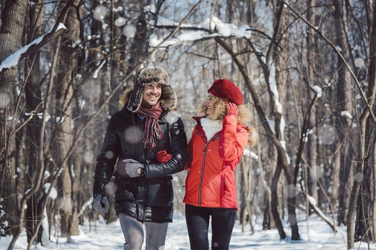 Couple having a winter walk on a chilly cold day in the woods