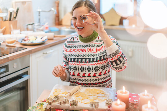 Woman in the Christmas kitchen posing with cookie cutter