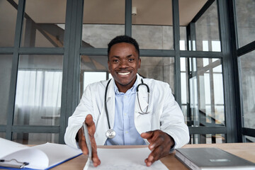 Happy african male doctor talking to camera during telehealth mobile consultation. Black physician...