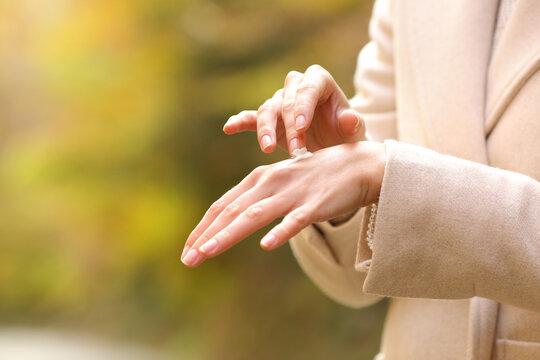 Woman hands in autumn applying moisturizer cream