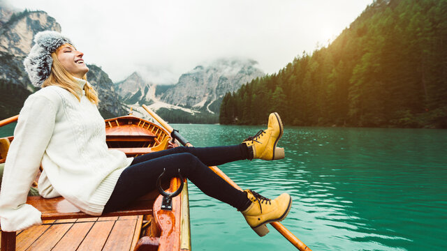 Tourist woman in traditional wooden rowing boat on italian alpine Braies Lake - Girl enjoying stunning view of Lago di Braies in Dolomites, South Tyrol, Italy, Europe.