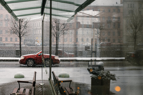 Car on a snowy dday in Saint Petersburg, Russia. Reflection seen in a glass bus stop.