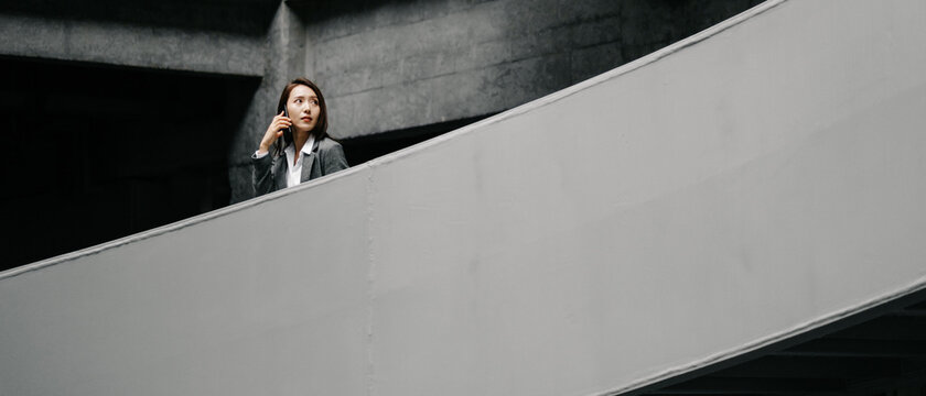 Businesswoman Using Cell Phone In Office Buildings