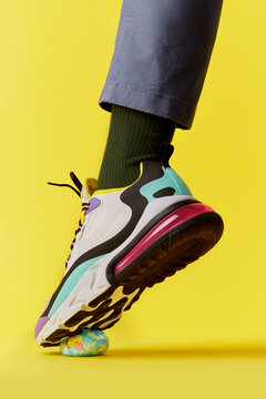 Foot in high fashion multi coloured trainer steps on the the world