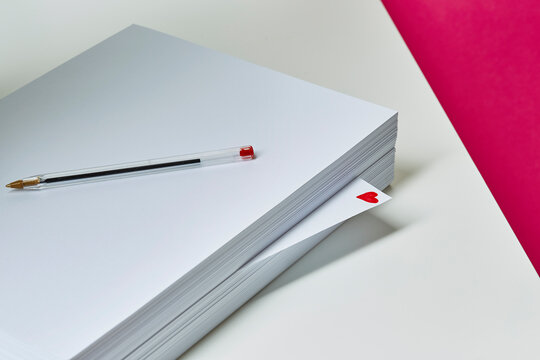 A ream of white A4 paper sits on a desk with a love heart scribbled on a single page.