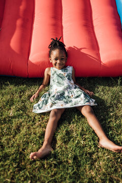 Little Girl in dress smiling in the jump house