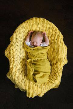 Cute baby sleeping on yellow plaid