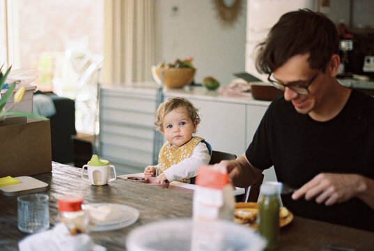 Father and one year old little girl in the kitchen at dining table
