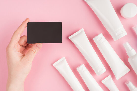 Cosmetics shop voucher concept. Top above overhead pov first person view photo of female hand holding voucher isolated on pink pastel background with white cream tubes
