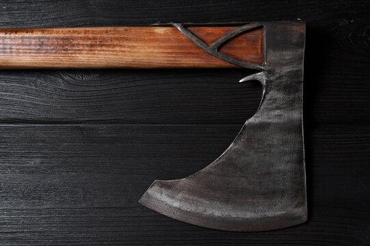 real scandinavian ax on a black wooden background, still life, viking ax