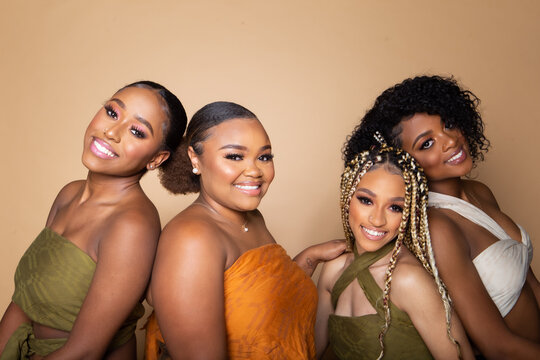 Studio portrait of four happy beautiful black female friends