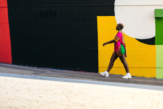 Young fashionable woman walking city street