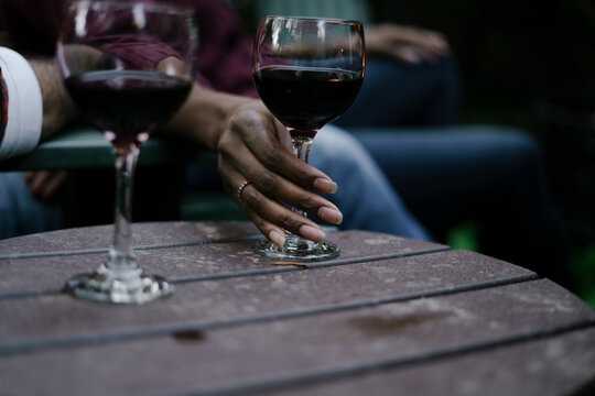 Black woman reaches for glass of red wine at party