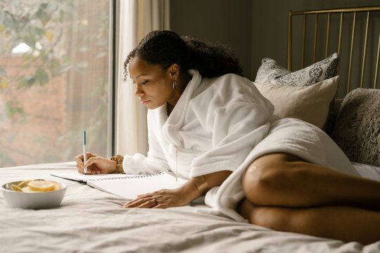 Black woman journaling at home in bed