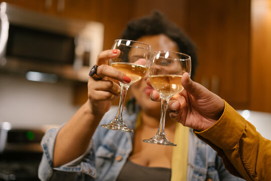 Black woman toasting with wine at a house party and get together with friends