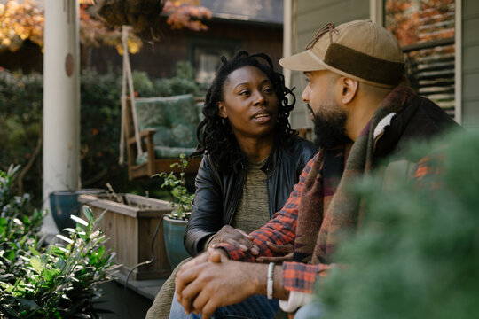 Beautiful black couple talking on front porch at home