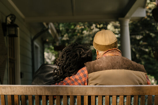 Black couple spending quality time together on front porch swing at home