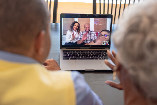 Grandmother and grandfather having a video chat  with family on laptop at home for Christmas