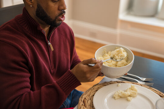 Black dad puts southern food on plate for Thanksgiving meal