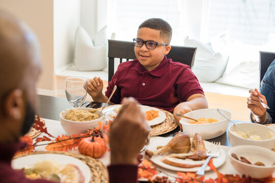 Multigenerational black family eating Thanksgiving dinner together at dining room table