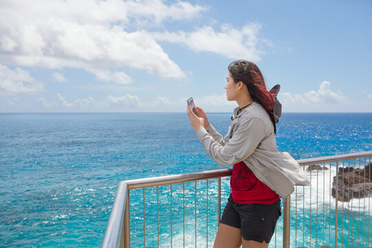 Teen girl at railing taking pictures by tropical ocean