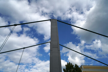 Low angle shot of a cable bridge column on a cloudy sky background