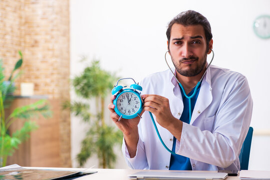 Young male doctor in time management concept