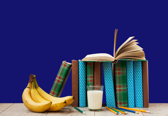Open book textbook in colorful cover, banana and a glass of milk on a blue background. Back to...